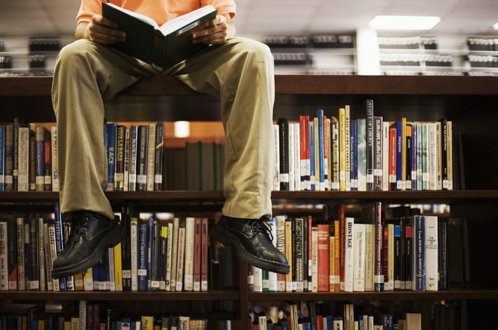 person-sitting-on-book-shelf-in-library